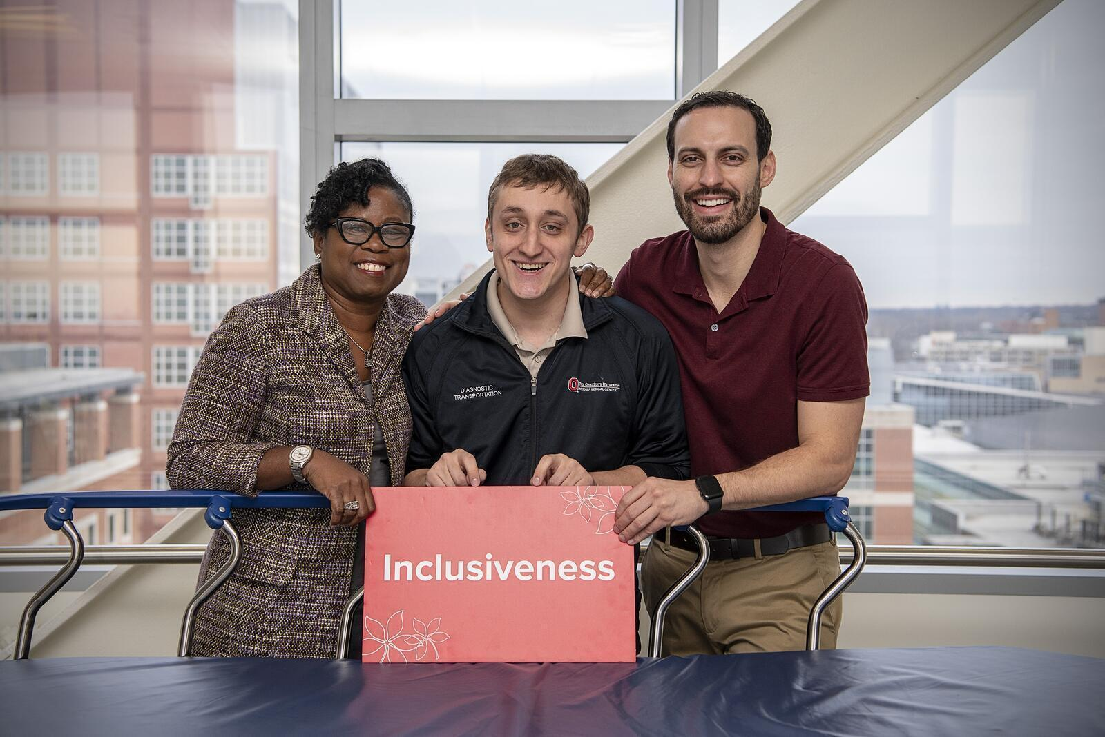 "Photo of Shelly Martin, Ben Walter and John Roese behind a patient transportation cart holding a red ""Inclusiveness"" sign"